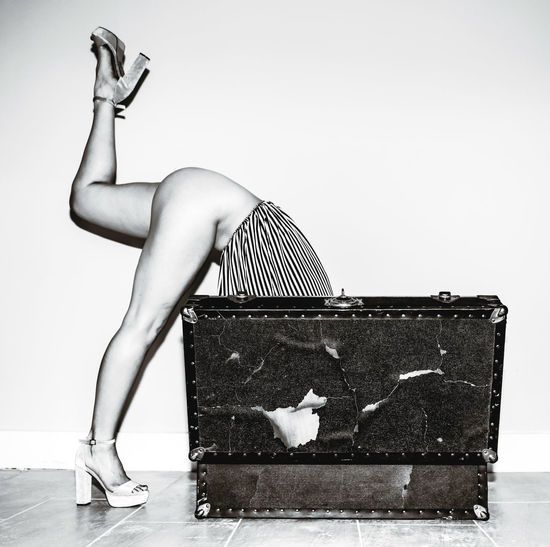 Low section of sensuous woman bending in suitcase against wall