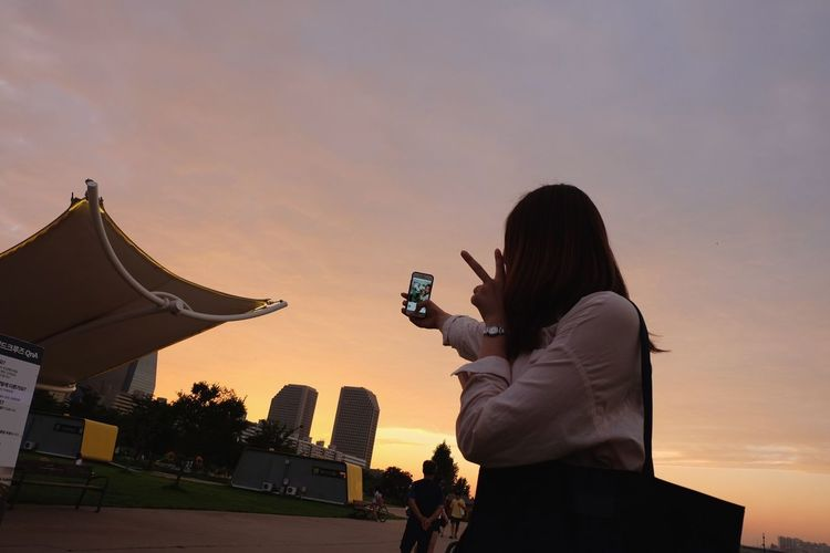 Capturing the moment Sunset People One Person Outdoors Sky Young Women Sunset Lovers Sunset Photography City Sunset Silhouette Travel Culture Of Korea One Woman Only Peace ✌ Peace Peaceandlove Pink Sky