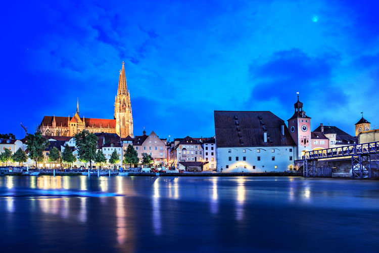 River against regensburg cathedral in city at night