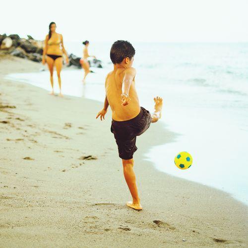 Boy kicking ball at beach