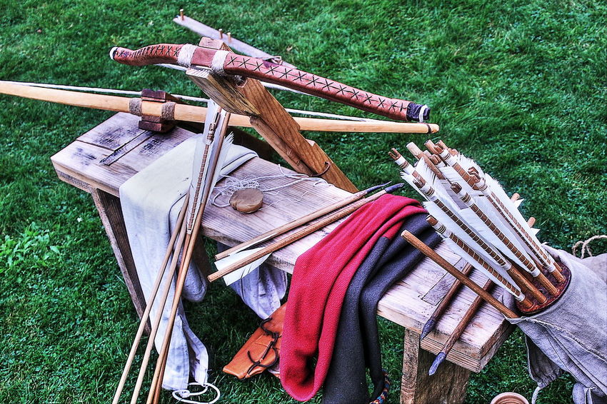 Readying for battle Arrows Bench Bow Crossbow Crossbow Bolt Day Feathers Field Fletcher Fletching Grass High Angle View Longbow Nature Nautical Vessel No People Outdoors Quiver String Wood - Material
