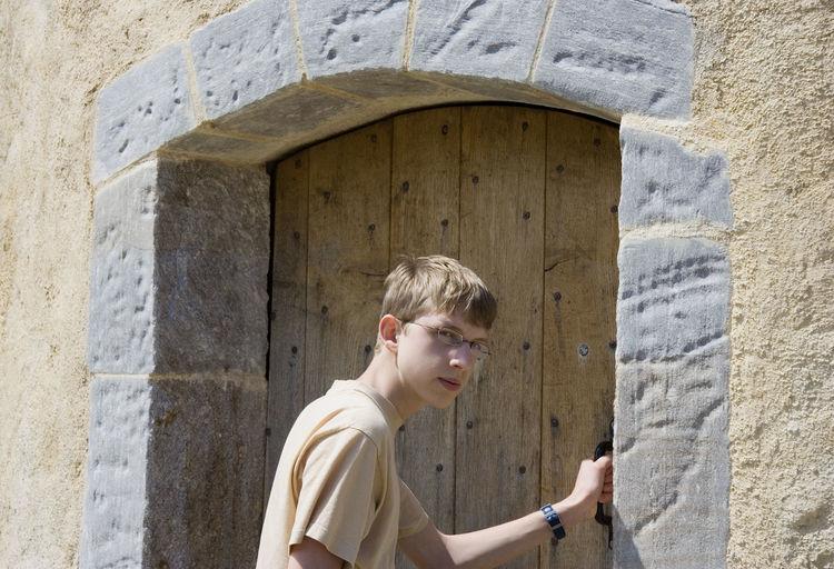 Portrait Of Teenager Holding Door Handle