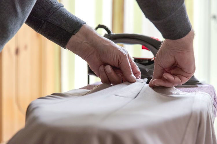 Grandpa help ironing dress for grandma in bright room at window. Focus on aged hands Adult Clothes Day Dress Feelings Flat Grand Father Handmade For You Help Home Housekeeping Human Body Part Human Hand Hygiene Indoors  Ironing Lifestyle Man Old Room Skill  Tailor Traditional Working Zipp