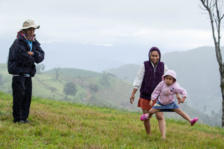 Full length of mother and daughter on mountain against sky