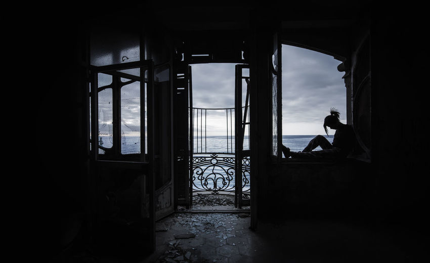 Silhouette woman sitting on window sill in abandoned home against sea