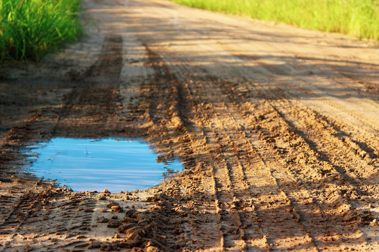 Surface level of dirt road in puddle
