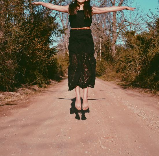 Cropped image of woman in black dress jumping with arms outstretched