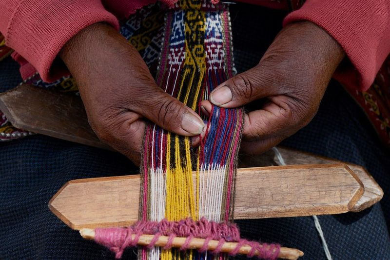 Midsection of person weaving textile in factory