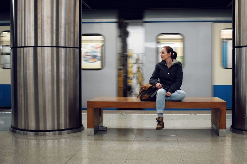 Full length of a young woman sitting on seat in the subway