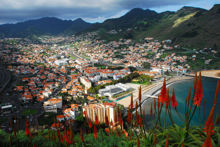 High angle view of townscape machico and mountains against sky