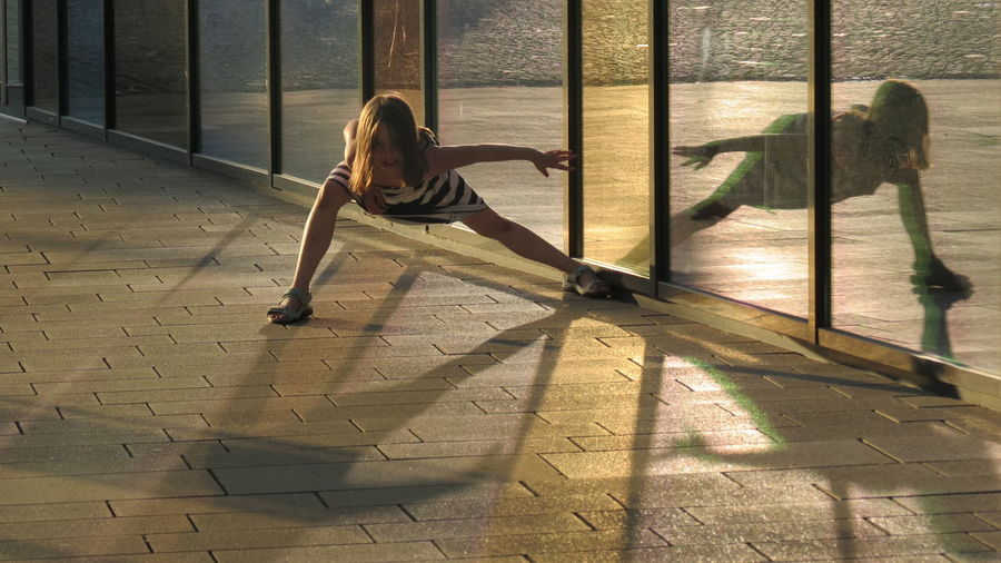 Full Length Portrait Of Girl Dancing With Reflection On Glass