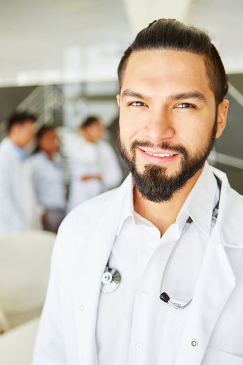 portrait of young man Apprenticeship Beard Boss Care Chief Chief Physician Clinic Clothing Colleagues Competence Confident  Doctor  Employee Executive  Facial Hair Focus On Foreground Front View Group Health Healthcare Healthcare And Medicine Hospital Incidental People Indoors  Interracial Job Lab Coat Leadership Looking At Camera Man Medicine Occupation People Physician Portrait Profession Professional Real People Responsibility Senior Physician Smile Smiling Staff Stethoscope  Team Trust Uniform White Woman Work Young Adult Young Men