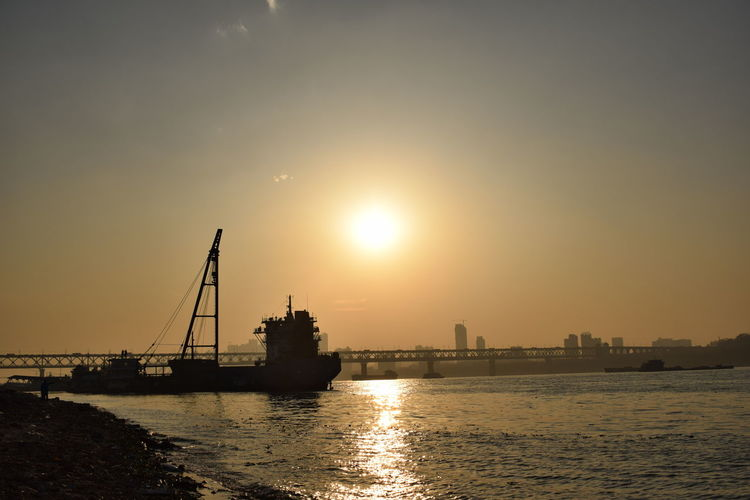 Scenic view of river against bright sun in sky during sunset
