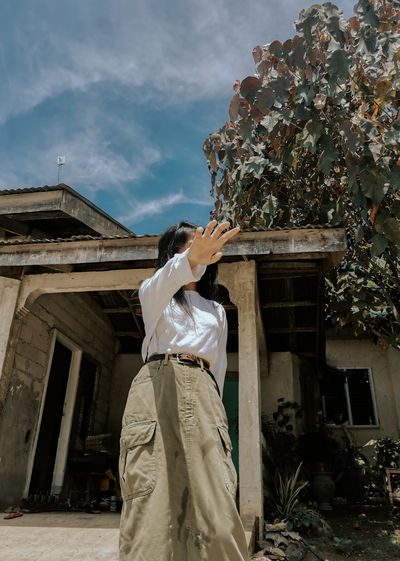 Low angle view of woman gesturing against house