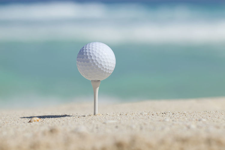 Golf ball sits on tee on sandy beach with surf in background