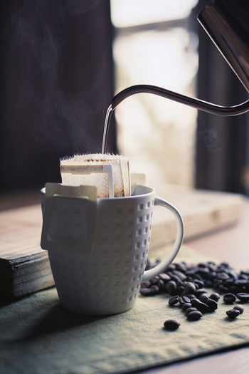 Hot water pouring drip bag coffee Breakfast Filter Kettle Pour Over Coffee Pouring Retro Smoke Aroma Close-up Coffee Coffee Bean Coffee Cup darkness and light Deep Drink Drip Bag Coffee Drip Coffee Extraction Flavor Food And Drink Hot Water Mug Roasted Coffee Bean Steam Swan Neck Kettle