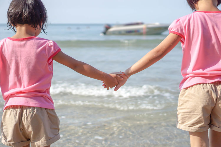 Two children shook hands along the beach with the sea as the background. Water Child Childhood Sea Two People Real People Beach Land Leisure Activity Rear View Lifestyles Girls Females Nature Women Casual Clothing Togetherness Boys Positive Emotion Outdoors Horizon Over Water