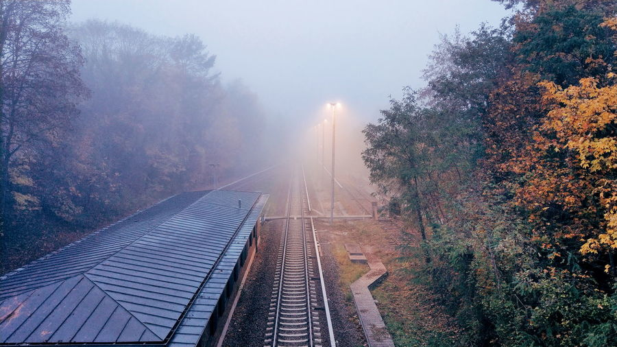 Railroad track amidst trees against foggy sky during autumn