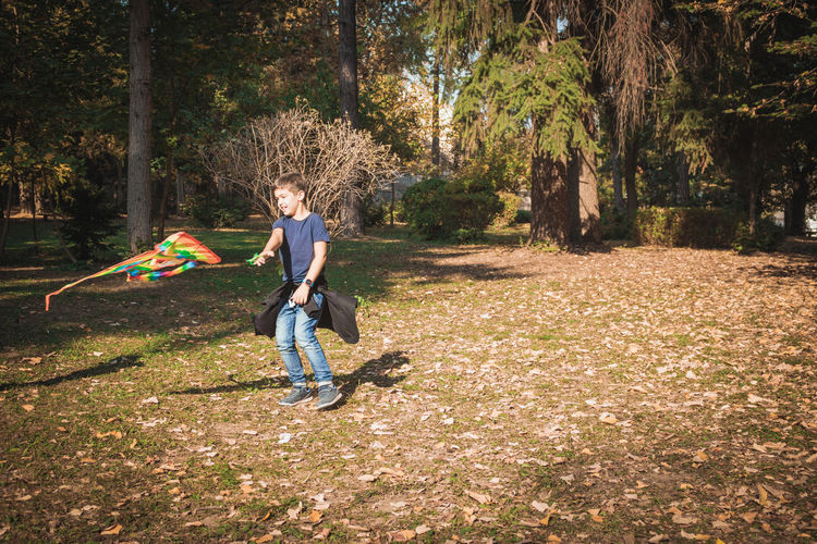 Full length of boy playing in forest