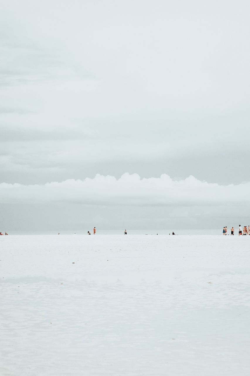 People At Beach Against Sky During Winter