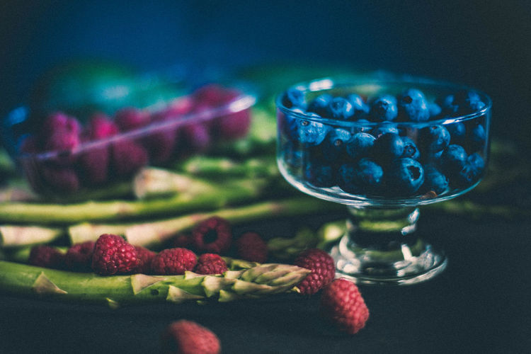 Close-up of berry fruits with asparagus on table