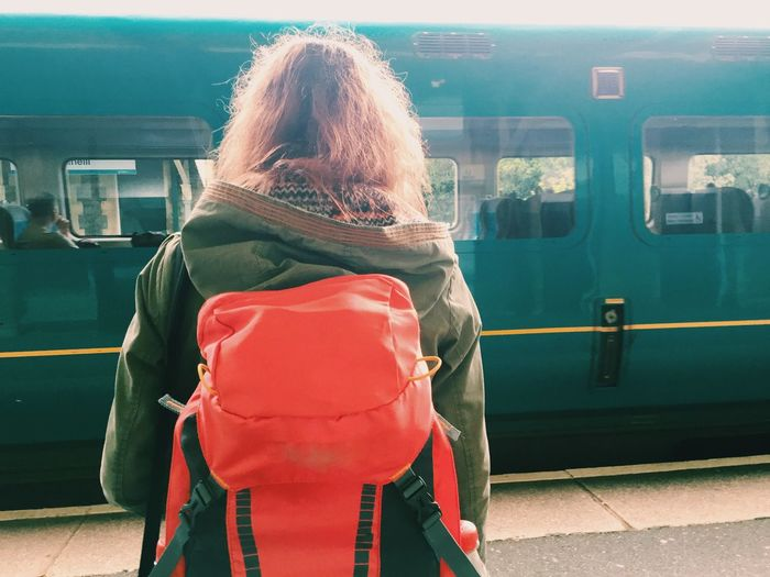 Rear view of backpack woman standing in front of train at station