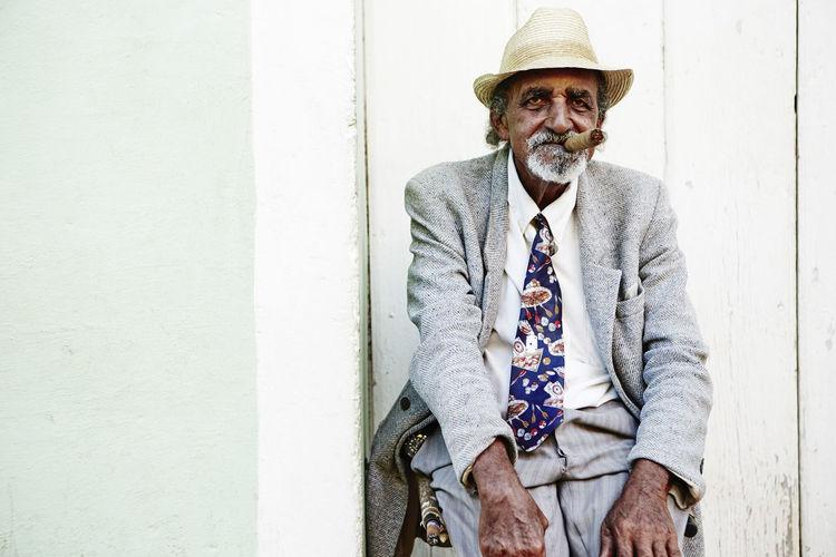 Portrait of man wearing hat sitting against wall