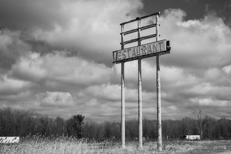 An abandoned roadside sign on the side of an American highway Antique Long Gone  Puffy Cloud Roadside America Travel Black And White Cloud - Sky Communication Day Environment Field Grass Land Landscape No People Non-urban Scene Nostalgia Outdoors Road Trip Sign Sky Text Tree Us Highway Western Script