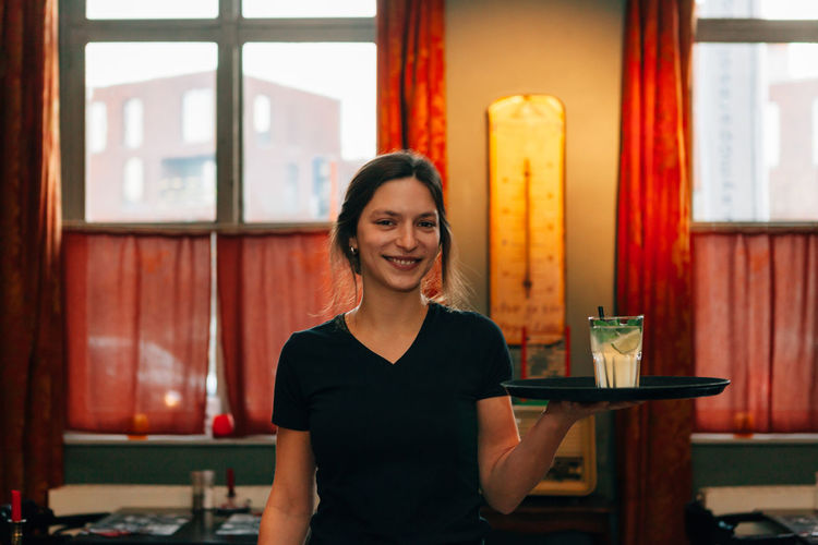 Portrait Of Waitress Smiling While Serving Drink In Restaurant