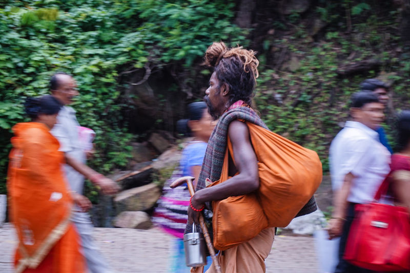 Side view of sadhu with bag walking by people on street