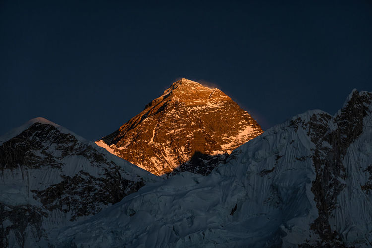 Tilt image of snowcapped mountain against clear sky at night during winter