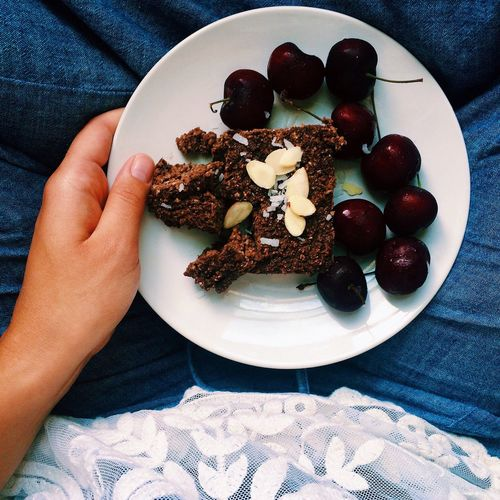 Personal perspective view of young woman enjoying slice of cake and cherries