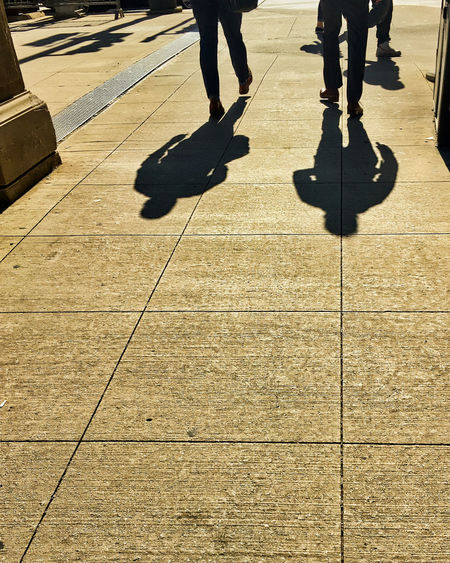 Shadows of two businessmen walking on city street. Waysofseeing City Body Part City Day Flooring Focus On Shadow Footpath Group Of People Human Body Part Human Foot Human Leg Lifestyles Low Section Men Nature Outdoors Paving Stone People Real People Shadow Shoes Suits  Sunlight Tiled Floor Walking The Portraitist - 2018 EyeEm Awards