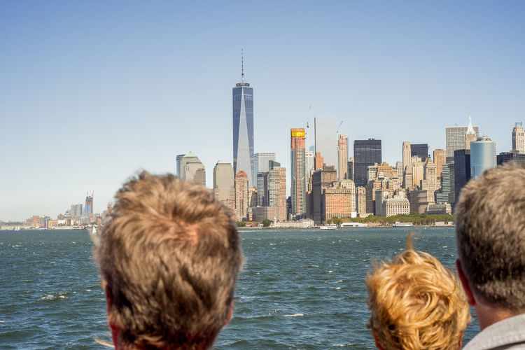 Rear view of people standing against sea and cityscape against clear sky