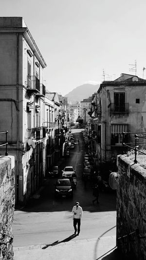 B&W. Streets of Palermo. Palermo, Sicily, Italy. Predestrian Sony Sonyalpha Sony A6000 Photographer Photo Photography EyeEm Selects EyeEm Best Shots Italy Sicily Palermo Black And White Blackandwhite Streetphotography Streets Light And Shadow Shadow City Full Length Architecture Building Exterior Built Structure Old Town Residential Structure Long Shadow - Shadow Residential Building Empty Road Human Settlement Townhouse