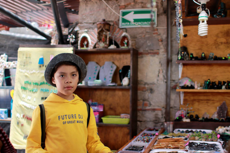 Portrait of boy standing at store in city