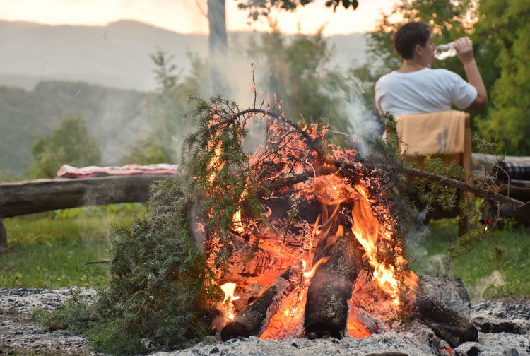 Rear view of man at forest with campfire in foreground