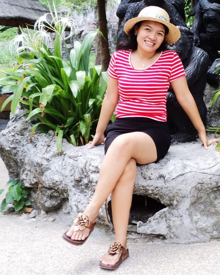 Portrait of smiling woman sitting against monkey sculptures