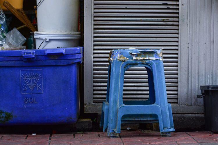 Garbage bin against blue wall in city