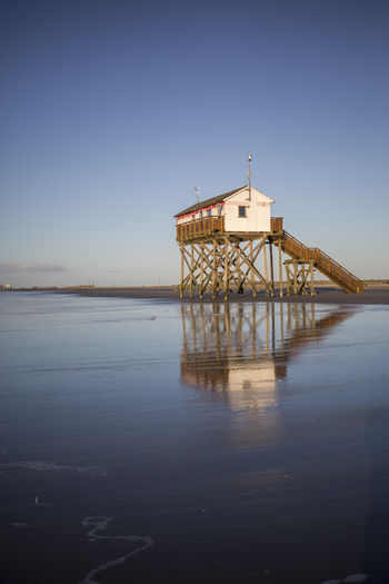 View of pier on sea against clear sky