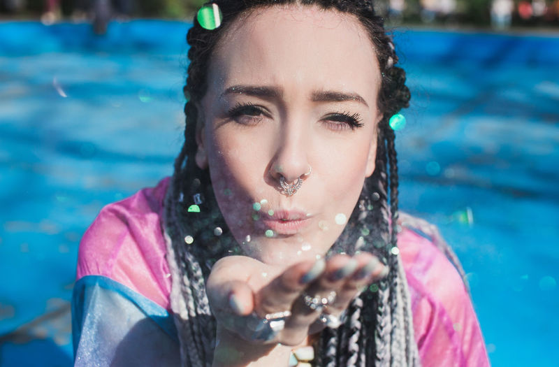 Beautiful woman with braided hair blowing glitter Braids Cool Glitter Hair Hands Pink Shining Sparkle Beautiful Woman Beauty Blowing Festival Glow Hairstyle Outfit Portrait Sunshine Turquoise Women Young Adult