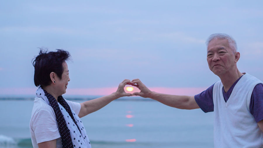 Optical illusion of man and woman holding dun in heart shape over sea against sky