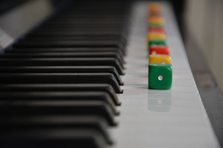 Close-Up Of Multi Colored Dices On Piano