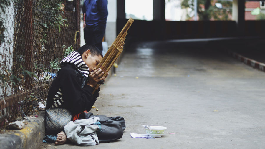 Beggar playing musical equipment while sitting on footpath