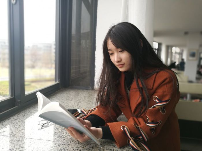 Young Woman Reading Book At Window Sill