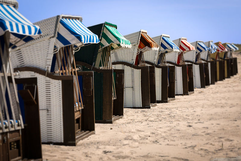 Hooded Chairs At Beach On Sunny Day