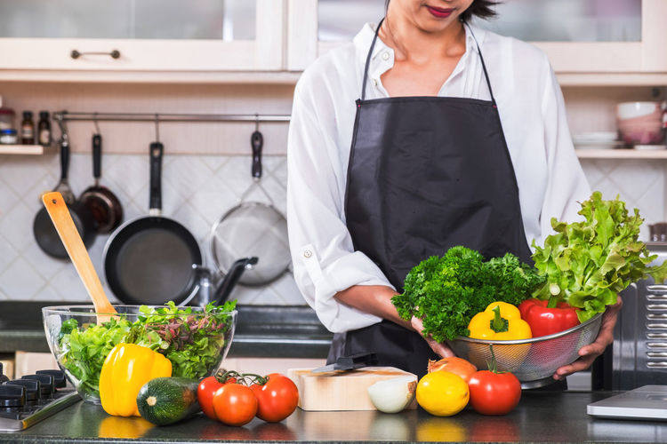 Midsection of woman holding vegetables in kitchen