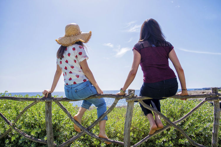 Rear view of two young woman sitting on a fence looking away against blue sky Two People Leisure Activity Togetherness Casual Clothing Sky Women Nature Real People Hat Rear View Lifestyles Adult Day Clothing Positive Emotion Young Women People Bonding Land Full Length Outdoors Couple - Relationship