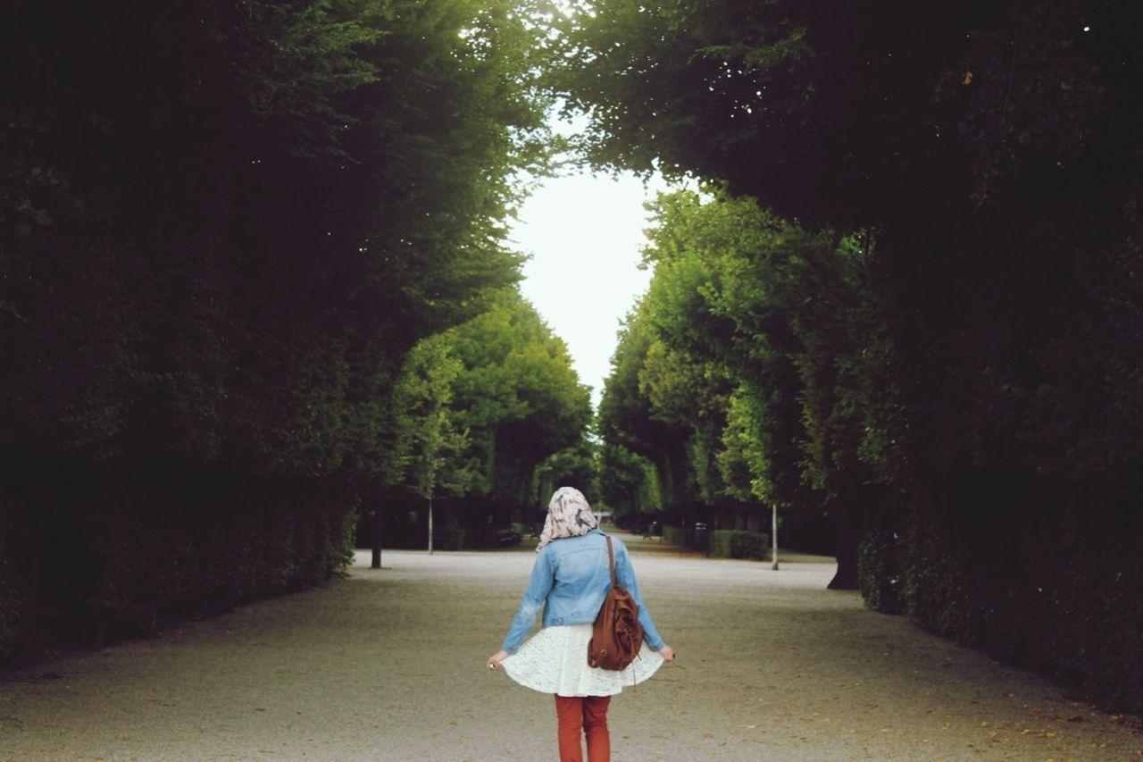 WOMAN WALKING AMIDST TREES