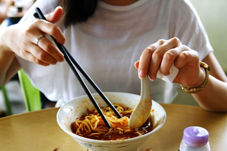 Midsection of woman holding chopsticks and spoon over hokkien mee bowl